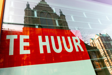 Large red To Let sign in a shop window written in the dutch language in the city centre of Rotterdam in The Netherlands