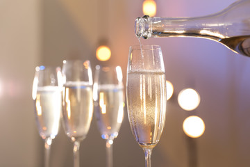 Champagne pouring from bottle into glass on blurred background, closeup. Space for text