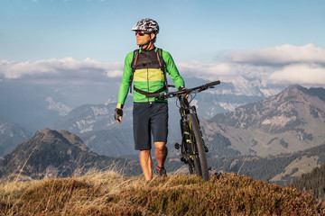 Male mountainbiker walking with his bike on a trail in the mountains