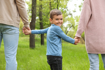 Fototapeta Happy little child holding hands with his parents in park. Family weekend obraz