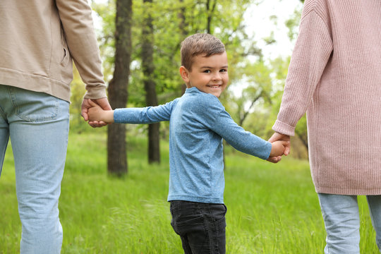 Happy little child holding hands with his parents in park. Family weekend