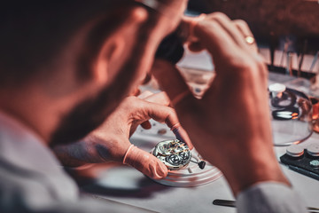 Mature clockmaster is fixing old watch for a customer at his busy repairing workshop.