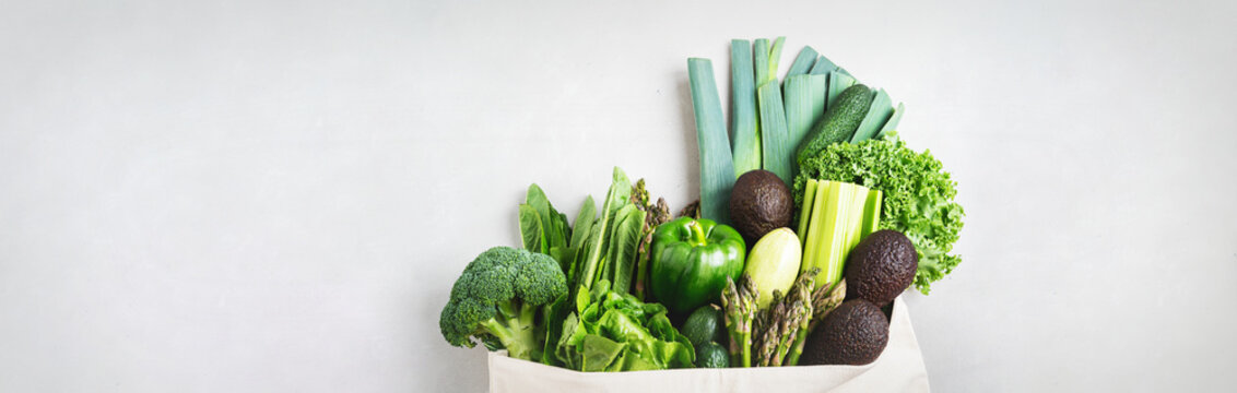 Variety of Fresh Vegetables and greenery in cotton eco bag on concrete background.Zero Waste shopping concept. Long wide banner with copy space.
