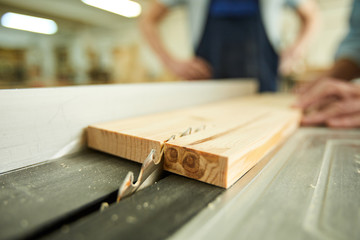 Obraz Closeup of unrecognizable carpenter cutting wood using disksaw in joinery workshop, copy space - fototapety do salonu