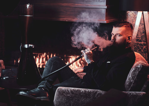 Handsome bearded man is relaxing on lounge while smoking hookah. He has tattoo on his hand.
