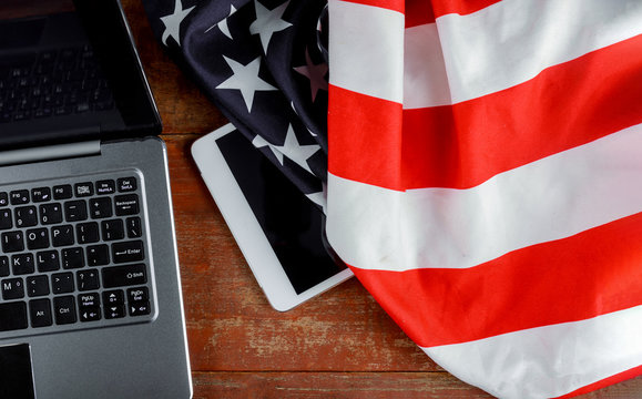 Tablet pc computer on american flag, technology, patriotism, anniversary, national holidays and independence day