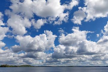 Blauer Himmel mit weißen bis grauen Wolken über dem Plöner See in Schleswig-Holstein. Es handelt sich um Haufenwolken bzw. Cumuluswolken.