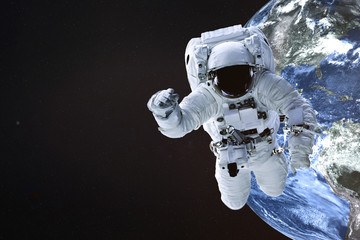 Astronaut near the Earth planet of Solar system. Science fiction. Elements of the image are furnished by NASA