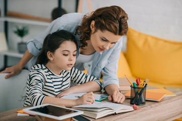 attentive mother helping adorable daughter doing schoolwork at home