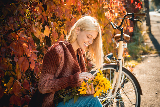 Girl with bicycle and flowers. Woman bicycle autumn garden. Active leisure and lifestyle. Autumn simple pleasures. Girl ride bicycle for fun. Blonde enjoy relax park. Autumn bouquet. Warm autumn