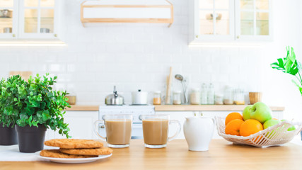 Two cups of morning coffee, cookies and fruit on the kitchen table. Good morning or breakfast concept.