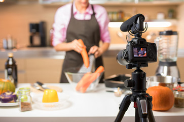 Woman recording video of her cooking for online video blog, focus on camera