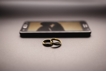 Concept of lovers or marital betrayal, infidelity. Pair of rings next to a smartphone, with an image of a blurred couple kissing on the screen.