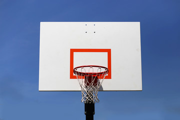 Outdoor Basketball Hoop and Backboard Isolated Against Blue Sky