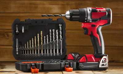 Cordless drill driver in red with rubberized handle in profile with drill bits set
