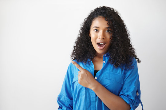 Check this out. Waist up shot of beautiful amazed young dark skinned female in blue shirt staring at camera in full disbelief, jaw dropped, pointing fore finger against white copyspace wall