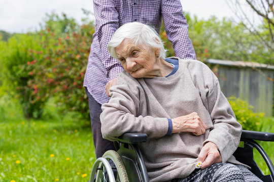 Old lady with dementia in a wheelchair and carer