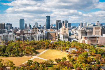 Osaka Cityscape in Kansai region, Japan - View from Osaka Castle with the park surrounding the castle in autumn in the foreground.