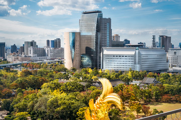 Rooftop View from Osaka Castle with the golden Shachi fish tail sculpture and Castle Park in autumn in the foreground, and Osaka Cityscape Landmark Buildings in the background in Japan.
