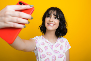 Beautiful funny young caucasian female doing a selfie smiling with a red smartphone isolated over a yellow studio wall.
