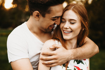 Obraz Portrait of a amazing couple laughing while man is embracing from back her girlfriend with red hair against sunset while dating in their vacation time. - fototapety do salonu
