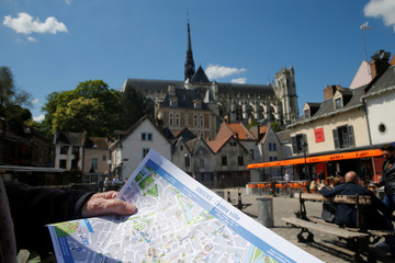 A tourist holds a map of the city of Amiens