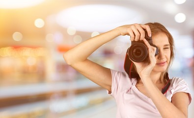 Woman with a professional camera takes pictures indoors