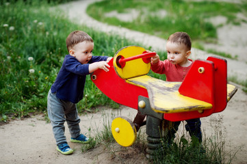 The two-year-old twin brothers play together on the playground. They are dressed in bright colors.