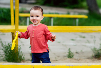 One-year-old boy is playing on a playground. He is dressed in a bright red shirt and blue jeans. He smiles funny.