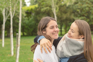 Christian friendship. Two happy women friends laughing and hugging outdoors.