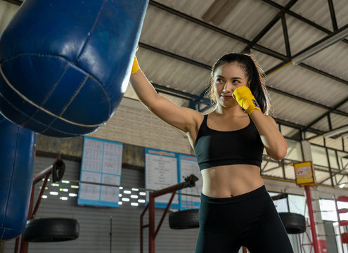 Fitness woman with the yellow boxing bandages,Female boxer in the gym.