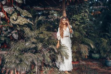 beautiful young cheerful boho style woman at tropical green leaves background