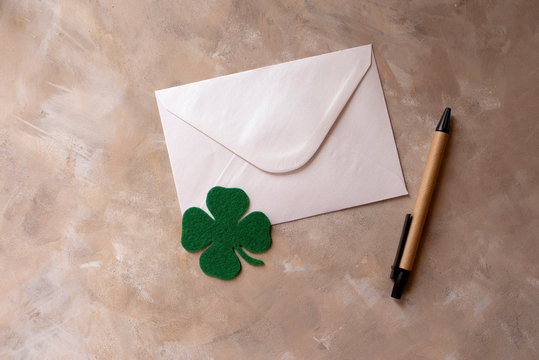 Letter and four-leaf clover on a light background