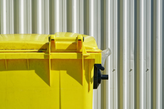Bright yellow dumpster against a white industrial corrugated cladding or wall siding.