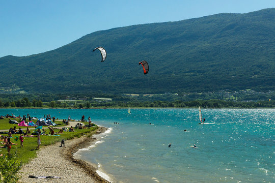Crowded beach of the lake Le Bourget with people playing on the grass, bathing, windsurfing and near Aix-les-Bains city with green mountains on the background. France.