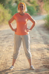 Cheerful senior woman in sportswear in the countryside. Active person keeping fit and healthy