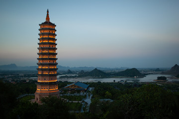 Evening view of illuminated Bai Dinh Pagoda and green landscape. Religious complex in Ninh Binh, Vietnam