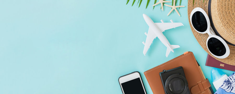 Top view of traveler accessories, tropical palm leaf and airplane on blue background with empty space for text. Travel summer holiday vacation banner concept.