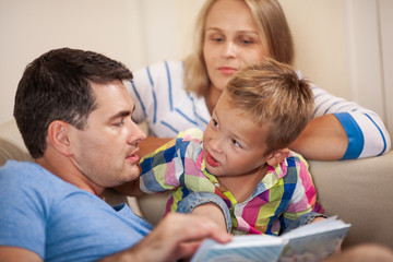 Little boy looking at father with curiosity during the evening book reading with a family