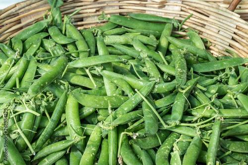 Fresh green peas on basket for sale on farmers market