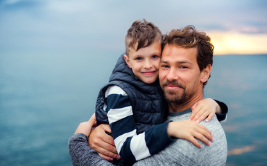 Father with small son on a walk outdoors standing on beach at dusk.