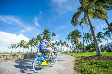 Tourists ride bicycles along the beachfront promenade in Lummus Park adjacent to historic Ocean Drive in South Beach, Miami, Florida, USA