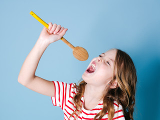 pretty cool and young girl uses cooking spoon as microphone and sings in front of blue background and is having a lot of fun