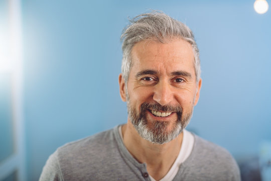 happy middle aged gray haired bearded man smiling against blue background