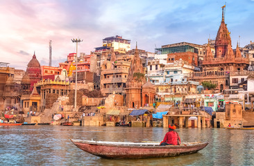 Ancient Varanasi city architecture at sunset with view of sadhu baba enjoying a boat ride on river Ganges. Wall mural