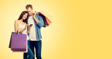 Picture of happy smiling couple with smartphone and shopping bags, against yellow color background