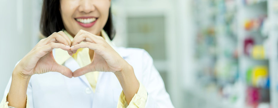 Portrait of a smiling young asian woman or Pharmacist showing heart gesture with two hands or making heart, expressing the concept of love and friendship and service on pharmacy background,advertising