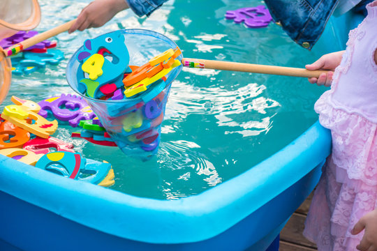 Educational water game for children. Fish in the form of letters of numbers and images of animals and a net for fishing. Fun for kids