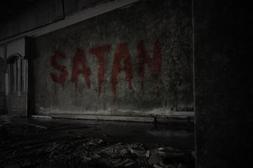 text satan on the dirty wall in an abandoned ruined house