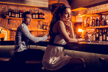 Woman feeling lonely without friends in the bar